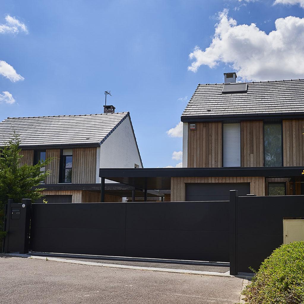 Portail noir horizon devant maison en bois