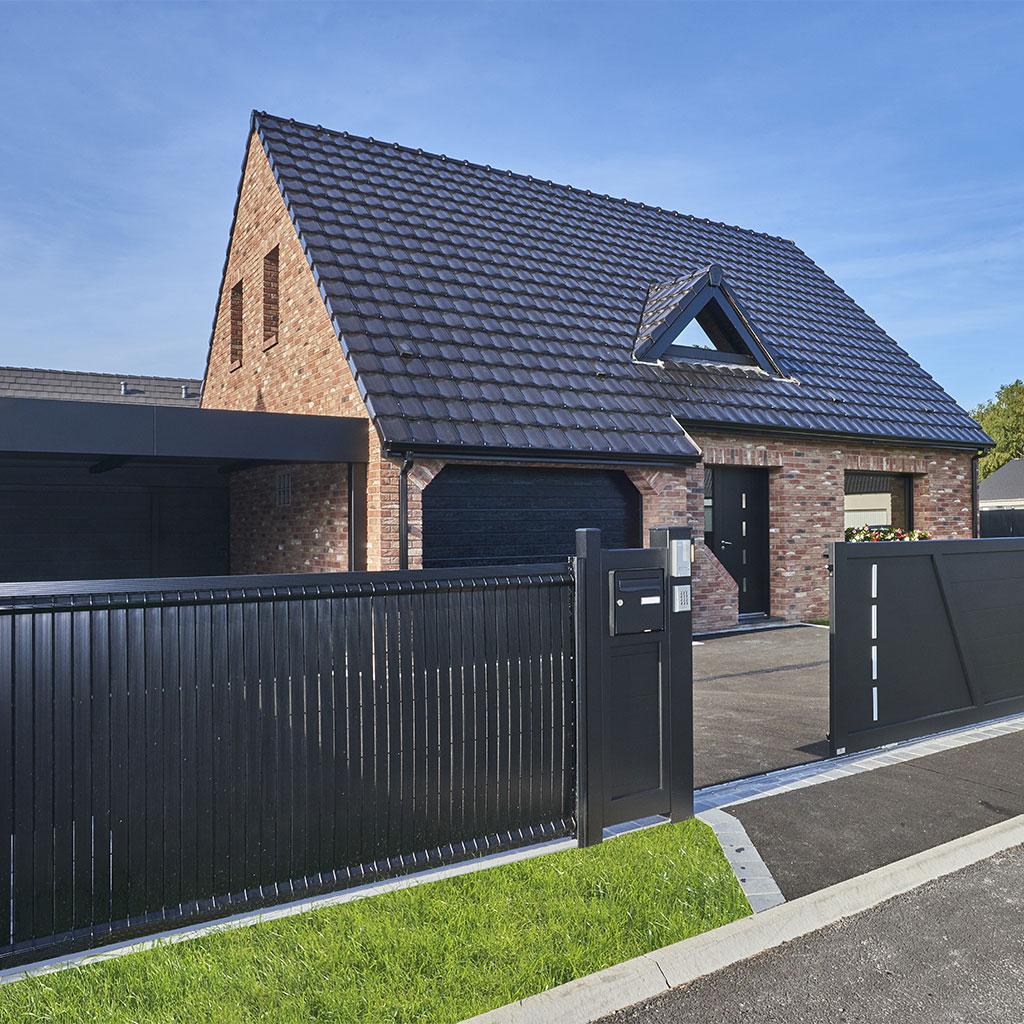 portail et clôture noir devant maison en briques